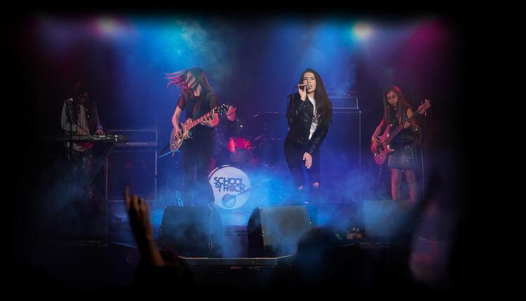 Los estudiantes actúan en una banda en el escenario.
