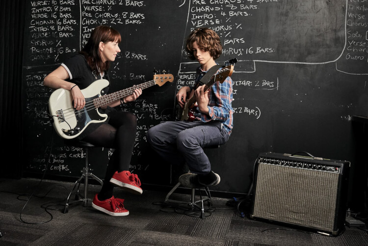 Instructor and student taking bass guitar lessons for kids