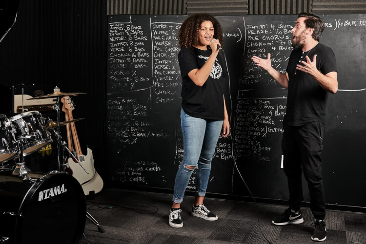 Instructor teaching advanced singing lessons to a teenager