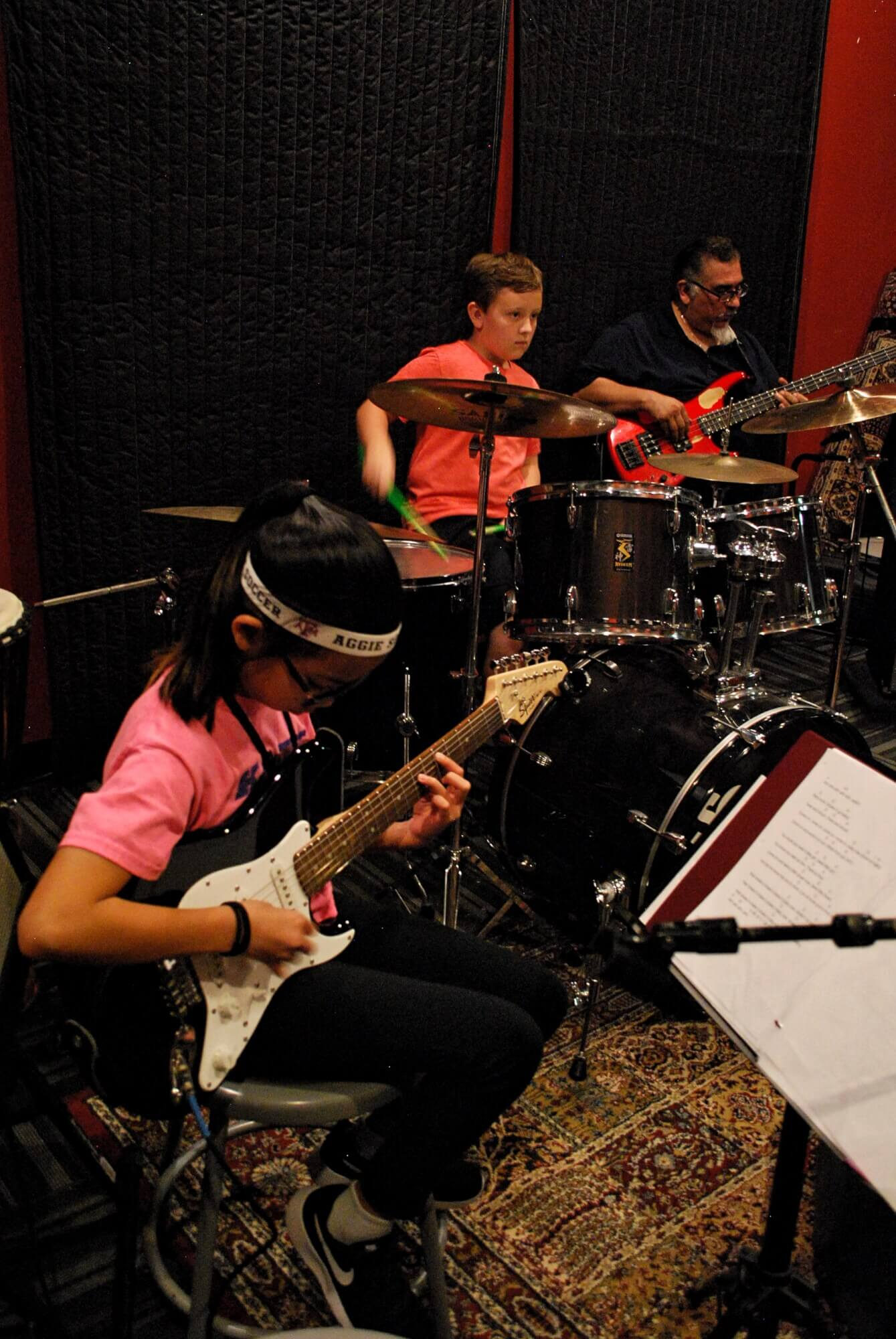 Rock 101 students work through their parts with Director Evetier Barron, laying down some bass.