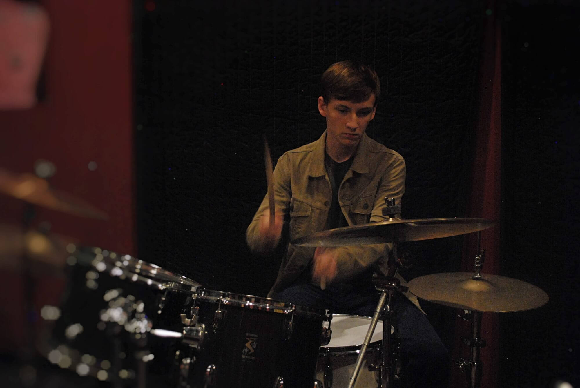 A Katy House Band student works on his drum fills during rehearsal.