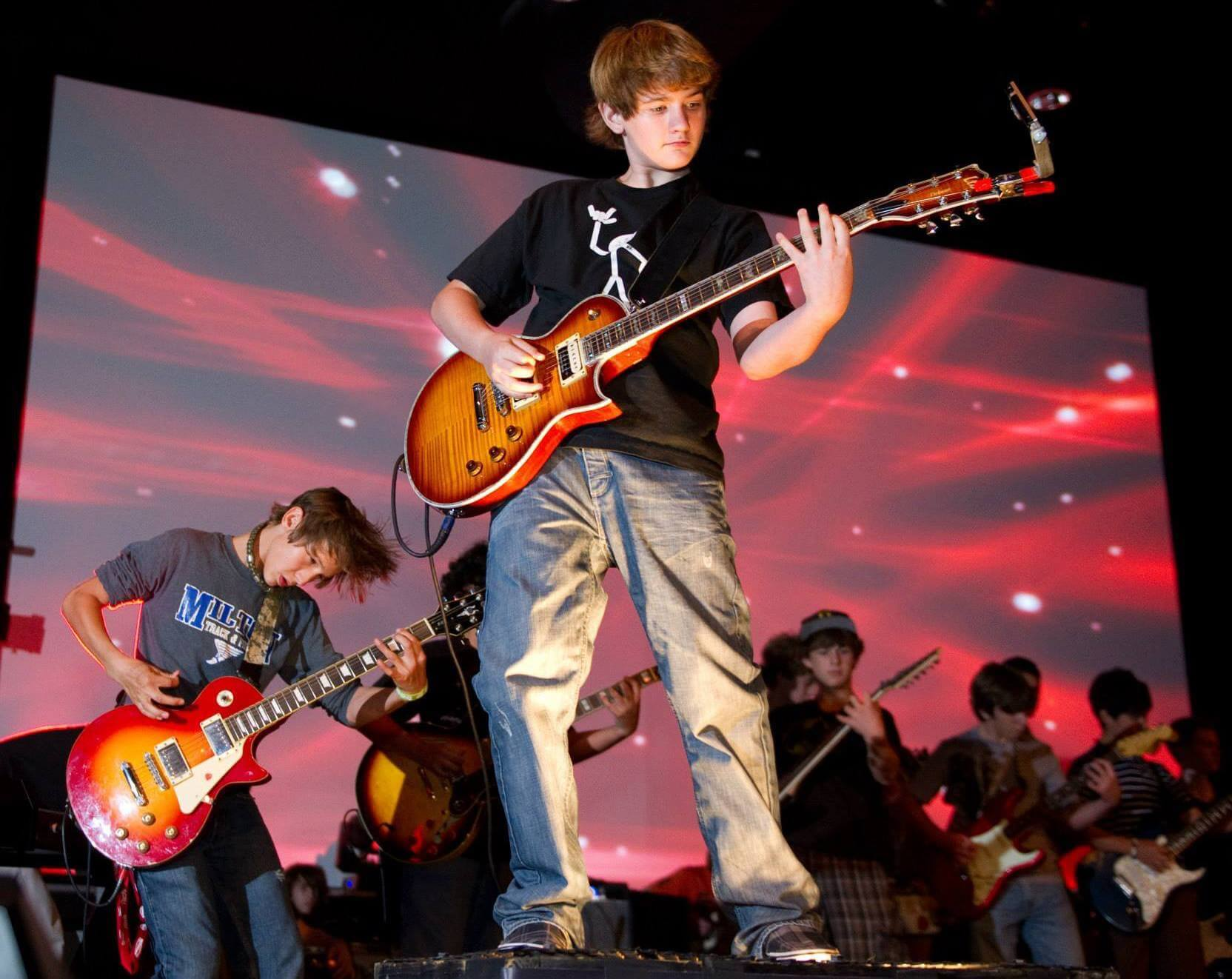 A featured guitarist solos at a Rock Camp concert.