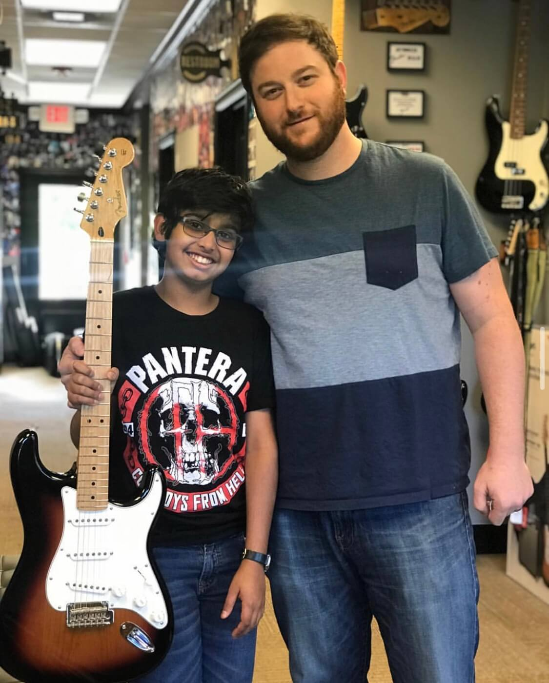 Adam and a student show off his sweet new Fender guitar.