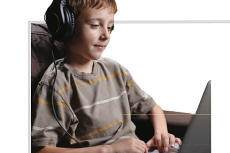 Kid listening with headphones typing on computer