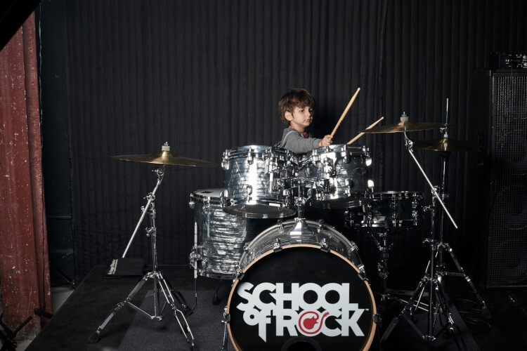 School of Rock student hitting a cymbal with a drum stick