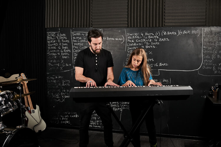 A School of Rock instructor teaches a child to play the keyboard