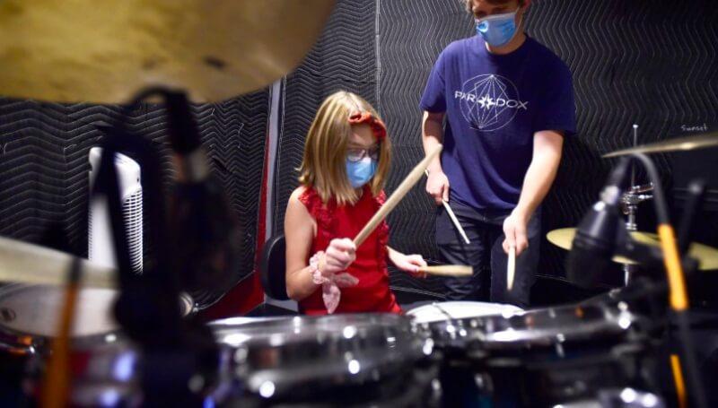 School of rock teacher practices drums with student