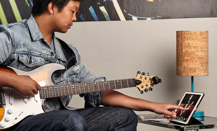 School of rock student learning to play guitar