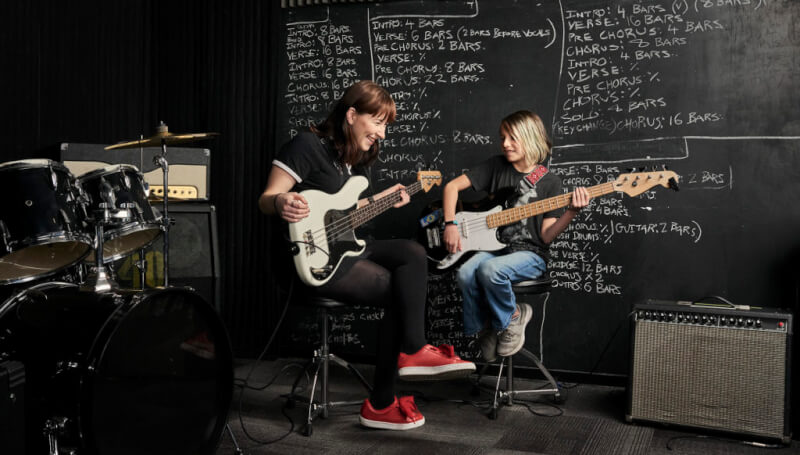 Guitar teacher playing guitar with student