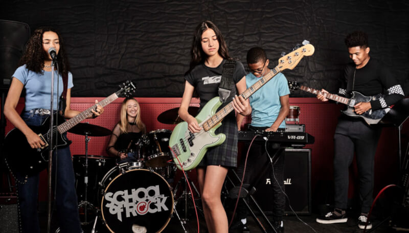 School of Rock students playing instruments in performance