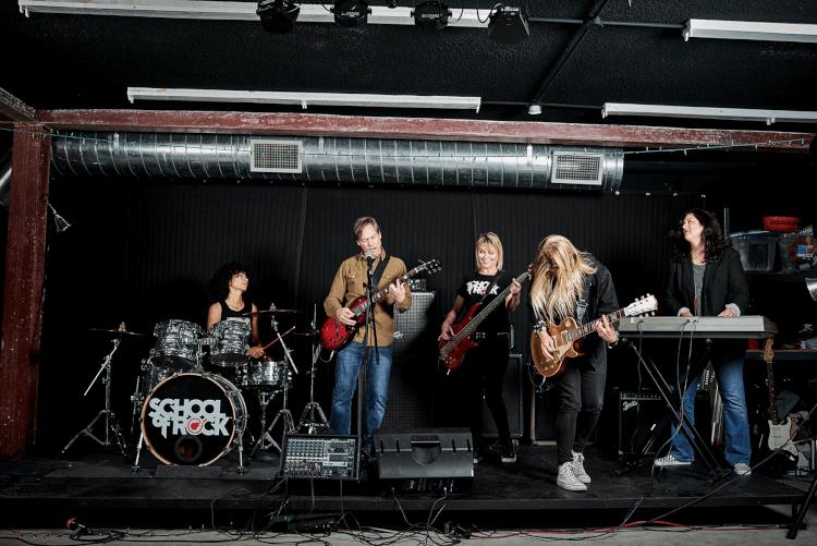 Alunos tocando no palco do Programa para Adultos da School of Rock