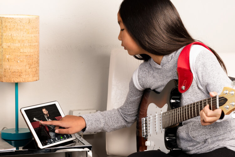 female student using iPad for video guitar lesson