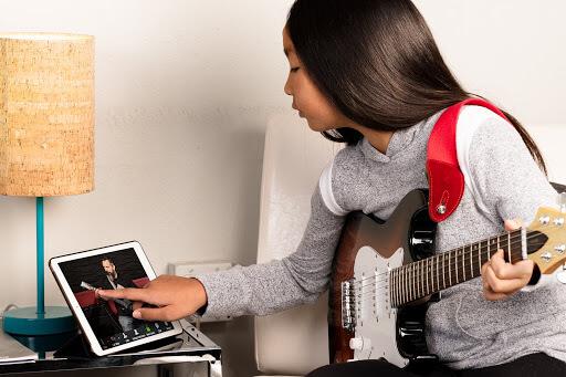 Garota utizando um Ipad durante sua aula de guitarra online