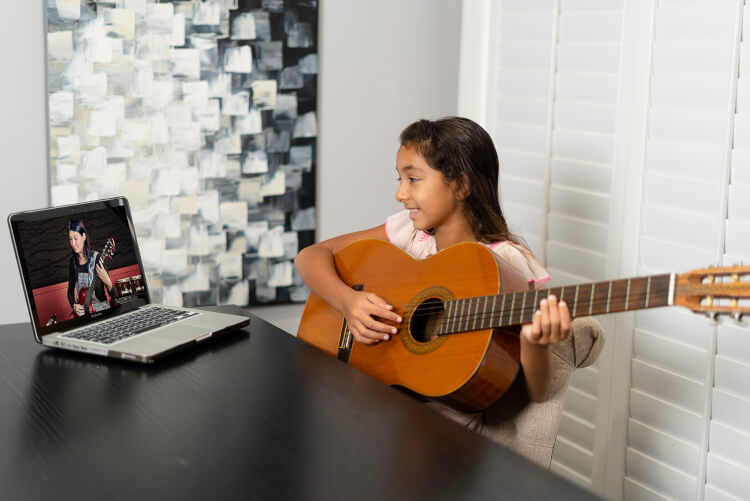 Student learning to play in online rock program for kids