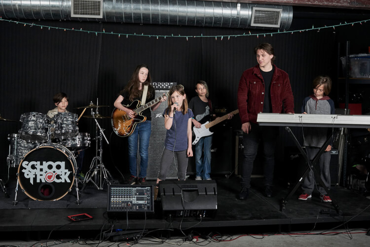 Students playing onstage in the rock 101 music program for kids