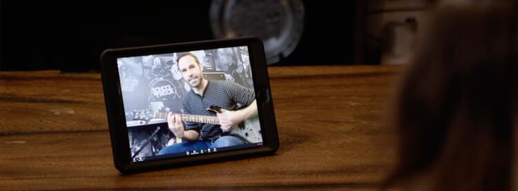 Aluno realizando sua aula virtual de guitarra