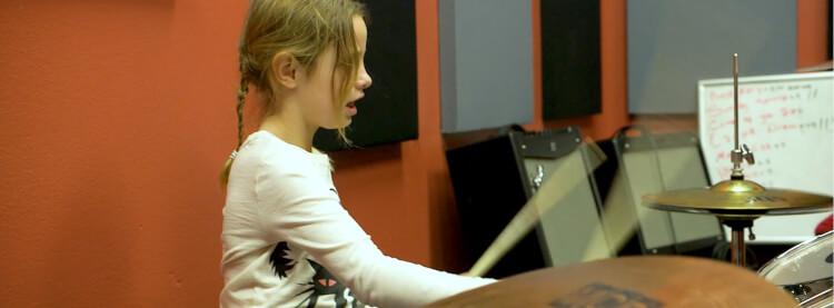Estudante da School of Rock tocando em um programa para alunos da segunda série